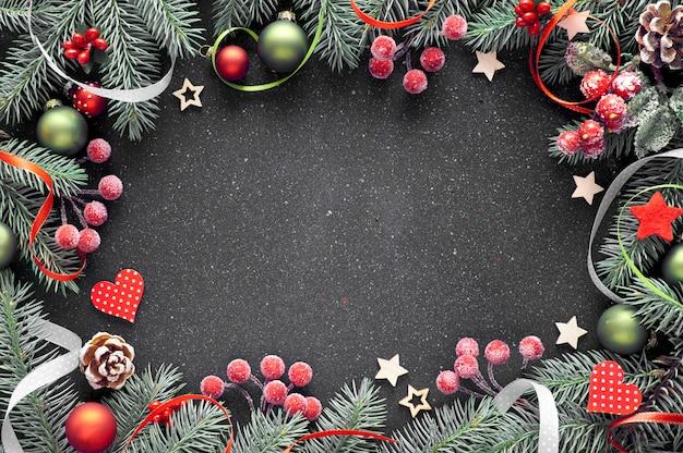 Новогодняя рамка с еловыми ветками, безделушками красного и зеленого цветов, звездами, сердечками, ягодами и лентами