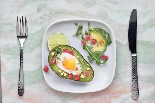 ハムキューブ、ウズラの卵、チーズを添えた焼きアボカドボート、グリーンルコラサラダ添え