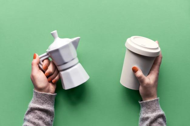 再利用可能なコーヒーマグまたは女性の手でカップと白いセラミックコーヒーメーカーを維持