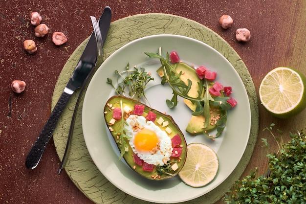 Диетическое блюдо кето: запеченный авокадо с кубиками ветчины, перепелиным яйцом и сыром, подается с зеленым салатом руккола