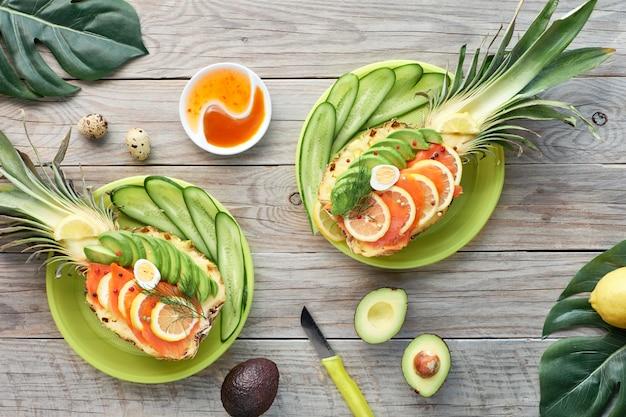 スモークサーモンとレモンとウズラの卵とアボカドのスライスとパイナップルボートの平面図、古い木製のテーブルに横たわっていた