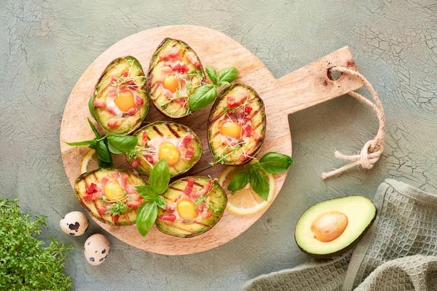 Вид сверху на авокадо на гриле лодки с беконом и перепелиными яйцами, фла