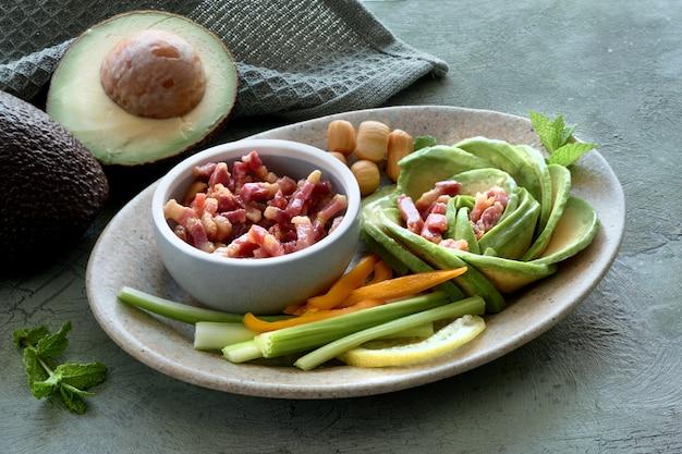 Кето диета, крупный план на авокадо, розовом салате с беконом и копченым сыром