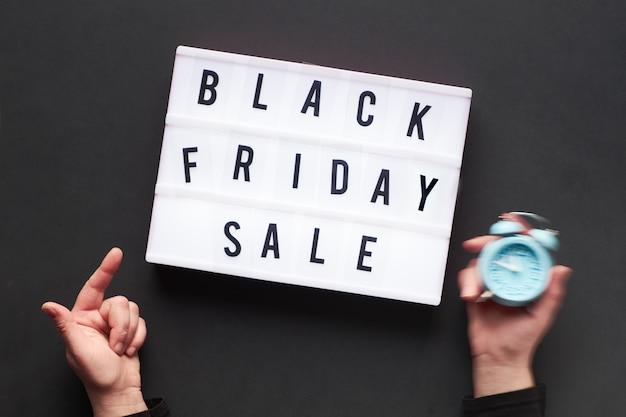 Текст в лайтбоксе «черная пятница распродажи» двумя руками, одна держит будильник, а другая указывает на текст в лайтбоксе.