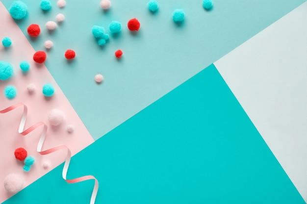 Вид сверху на красочные пушистые шарики, плоские лежал на фоне пастельных тонов геометрической бумаги с копией пространства