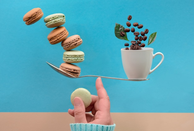 Балансировка чашки кофе и макарон на пальце