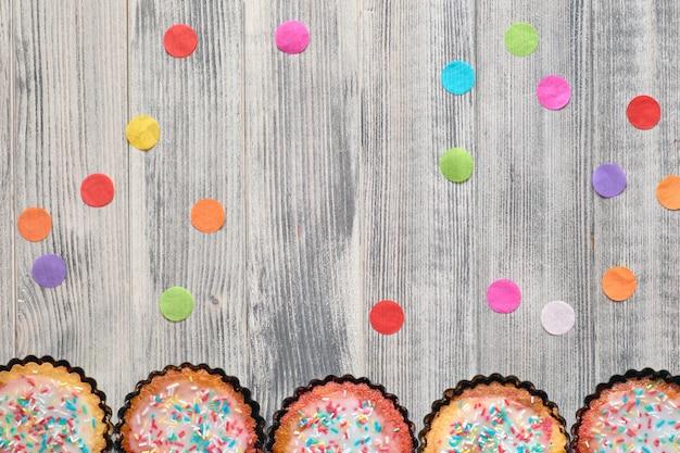 Плоская кладка с бумажным конфетти и маленькими пирожками-попугаями с посыпанным сверху цветным сахаром на белой древесине