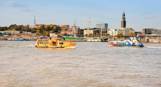 Лодка с туристами идет по реке эльбе в гамбурге, германия