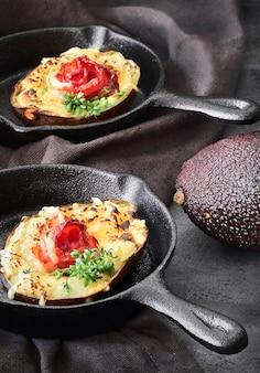 Кето диетическое блюдо: авокадо лодки с хрустящим беконом, плавленым сыром и ростками кресс-салат на темном
