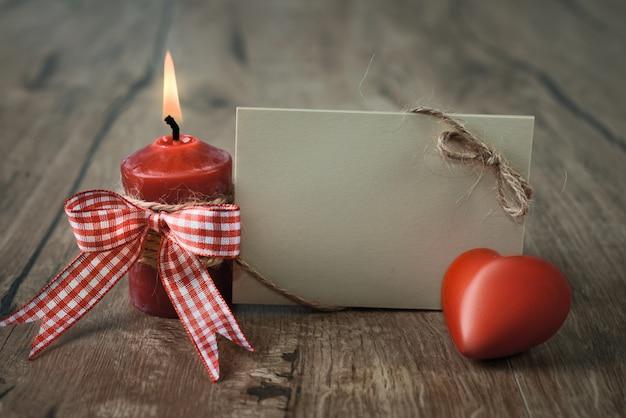 Пустая открытка с горящей свечой и красным сердцем