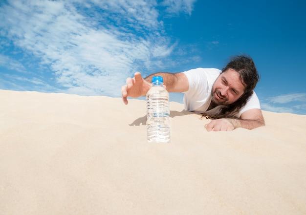 Жаждущий человек в пустыне хватает бутылку с водой