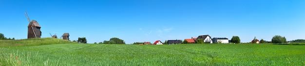 歴史的な風車と春の小麦畑の背後にある田舎の家の屋根のパノラマ画像。