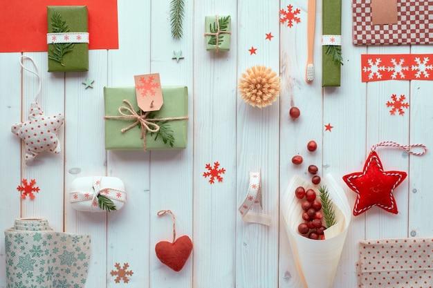 さまざまなクリスマスや新年の冬休みの環境に優しい装飾、クラフトペーパーパッケージ、手作りまたは廃棄物ゼロのギフト。白い木製の板、緑の葉と手作りの装飾にフラットレイアウト。