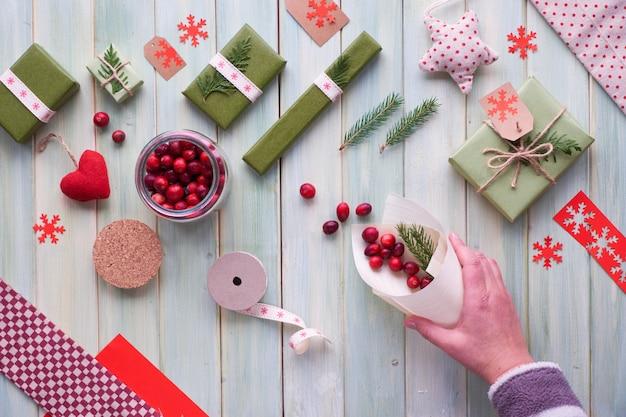 さまざまなクリスマスまたは新年の冬休みの環境に優しい装飾、クラフト紙パッケージ、再利用可能な、または廃棄物ゼロのギフト。フラットは木材の上に置き、手はモミの小枝と合板コーンにクランベリーを置きます。