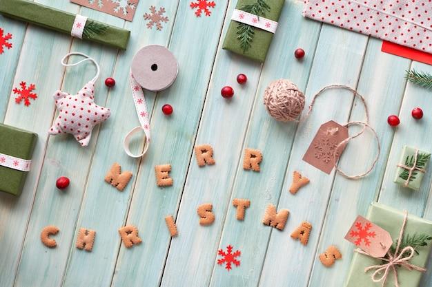 さまざまなクリスマスまたは新年の冬休みの環境に優しい装飾、クラフト紙パッケージ、再利用可能な、または廃棄物ゼロのギフト。緑の木製の板、クッキーで作られたテキスト「メリークリスマス」に横たわっていた。