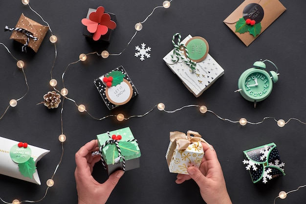 Новогодние или рождественские подарки, завернутые в различные бумажные подарочные коробки с праздничными бирками. руки держат коробки. праздничная планировка, вид сверху с легкой гирляндой, будильник и снежинки на черной бумаге.