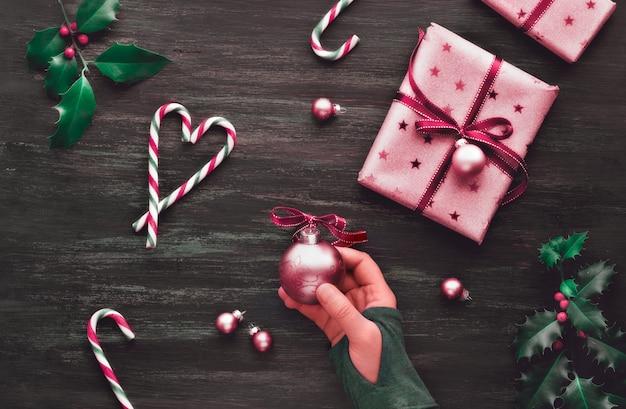 ピンクのギフトボックス、ストライプのキャンディー杖、装身具、装飾的な星、コピースペースを持つ創造的なフラットレイアウト
