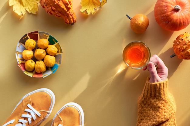 Женская рука с чашкой чая, оранжевыми тыквами, айвой и кроссовками из брезента