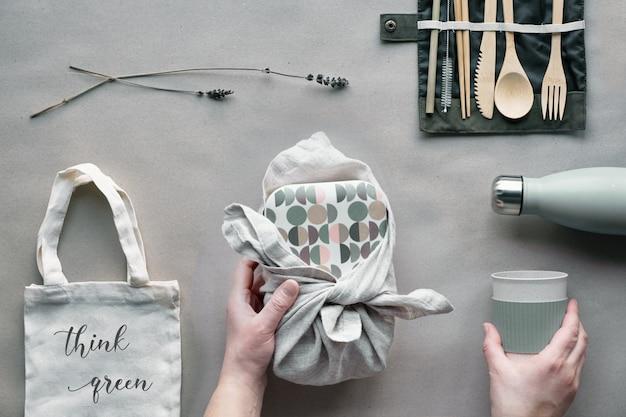 Творческий вид сверху, упакованный ланч с нулевыми отходами, коробка для ланча на вынос на хлопчатобумажной сумке, органайзер из бамбуковых столовых приборов, многоразовая коробка и бамбуковая чашка. устойчивый образ жизни, плоская планировка на крафт-бумаге.