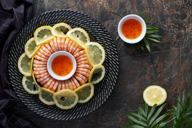 おいしいエビのリングは、暗いプレートにレモンと甘いチリソースを添えて提供します。