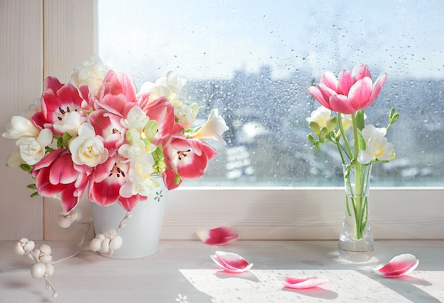 Розовые тюльпаны и белые цветы фрезии на подоконнике