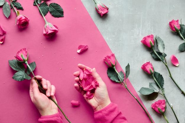 石の斜めの幾何学的な紙。ピンクのバラと花びらを保持している女性の手でフラットを置きます。挨拶の概念バレンタインの日、誕生日、母の日または他の小さな機会の平面図。