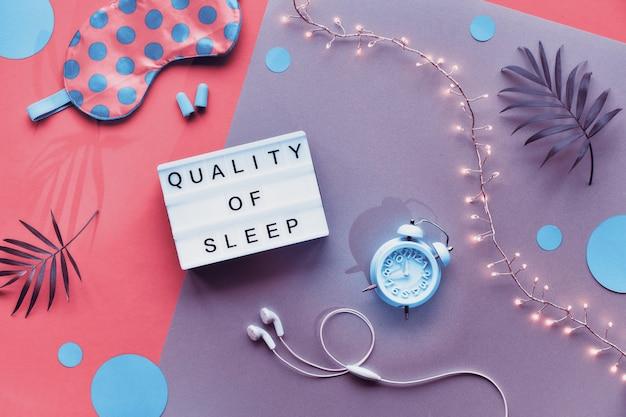 「睡眠の質」というテキストのあるライトボックス。健康的な夜の睡眠創造的なフラットレイアウト。スリーピングマスク、ブルーミント目覚まし時計、イヤホン、耳栓。スプリット