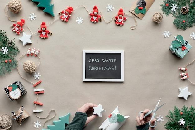 コピースペースでゼロ無駄なクリスマスフレーム。フラット横たわっていた、茶色のクラフトペーパーのトップビュー。繊維装身具、常緑樹、紙のギフトボックスを手に。環境にやさしいクリスマス、黒板に「ゼロ廃棄物クリスマス」。