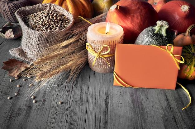 色あせた素朴な木の上の袋にカボチャ、小麦の耳、レンズ豆の秋収穫静物