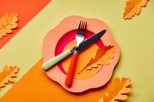 秋のお祝いのテーブルのセットアップ。紙と黄色い紙の上の明るいプラスチックプレート