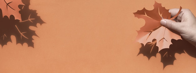 紙のコピースペースとフラットレイアウト、影で秋の休暇を持っている手