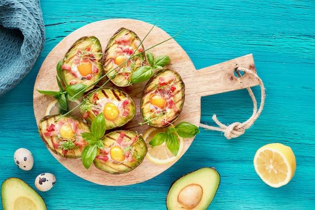 Вид сверху на авокадо на гриле лодки с беконом и перепелиными яйцами