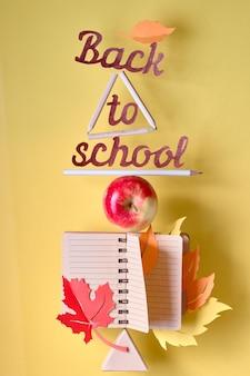 Вырезанный текст «обратно в школу» среди балансирующих стационарных объектов и яблока