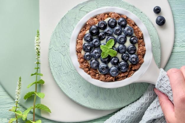 バニラカスタードクリームとミントの葉とおいしいブルーベリーのタルトのフラットレイアウト