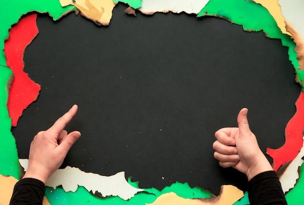 Обожженная бумага с белой, красной, желтой и зеленой бумагой с обожженными краями, черная бумага с копией пространства, руки, показывающие знак ок и указывающие на пространство копии ...