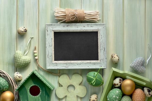 イースターフラットは、春の装飾と「ハッピーイースター」のテキストと黒板と明るい緑の木製の板に横た