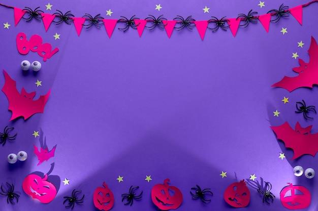 紫、赤、黒、フラットで創造的なハロウィーンフレームはコピースペースで横たわっていた。チョコレートの目、コウモリのペーパークラフトフィギュア、ジャックランタンカボチャ、星と旗とクモのガーランド。