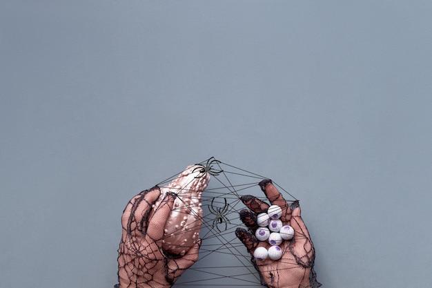 Творческая квартира хэллоуина лежала в розовом и черном на серой бумаге с копией пространства. руки в черных сетчатых перчатках держат розовую тыкву и горсть шоколадных глаз.