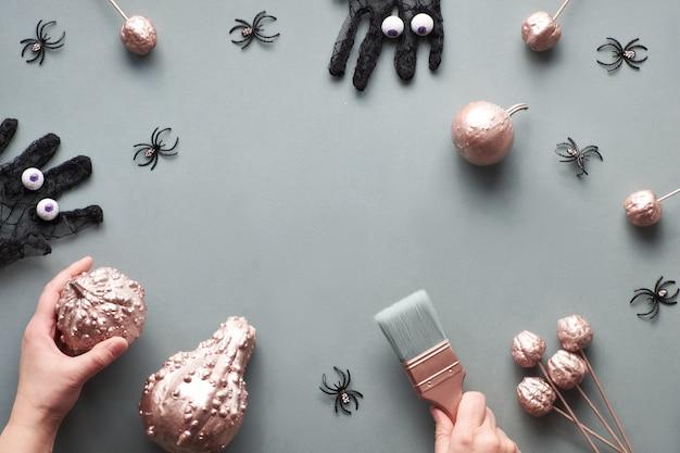Творческая квартира хеллоуина лежала на серой бумаге с экземпляр-космосом. рамка из розовых золоченых тыкв, черные сетчатые перчатки с шоколадными глазками, рука с кисточкой и несколько черных пауков.