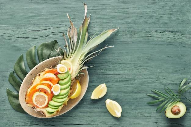 Вид сверху на ананасную лодку с копченым лососем, авокадо, лимоном и перепелиными яйцами, копией пространства