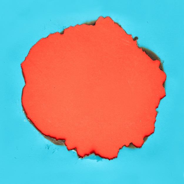 中央に焦げ穴のある鮮やかなカラーペーパー
