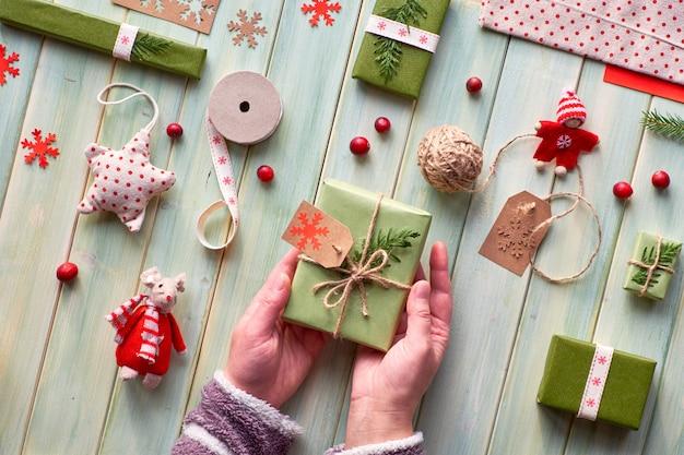 さまざまなクリスマスまたは新年の冬休みの環境に優しい装飾、クラフトペーパーパッケージ、さまざまな手詰めのゼロ廃棄物ギフト。木の上に横たわり、緑の葉で飾られたギフト用の箱を手に持つ。