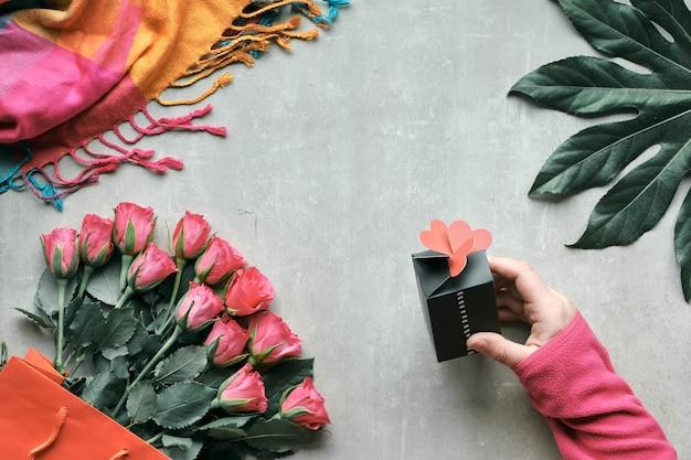 Плоская планировка, натюрморт с букетом роз и экзотическими листьями растений. рука держит небольшую подарочную коробку с сердечками на вершине. вид сверху на светлый камень. валентина, день рождения или день матери концепции.