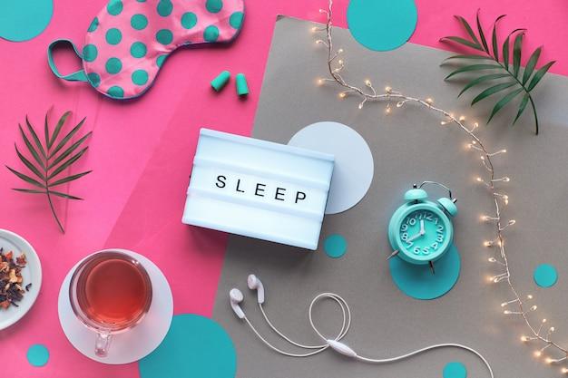 ライトボックス、テキスト「スリープ」。健康的な夜の睡眠創造的なフラットレイアウト。睡眠マスク、目覚まし時計、イヤホン、耳栓、ハーブティー。分割ピンクとクラフトペーパーライトガーランドとヤシの葉