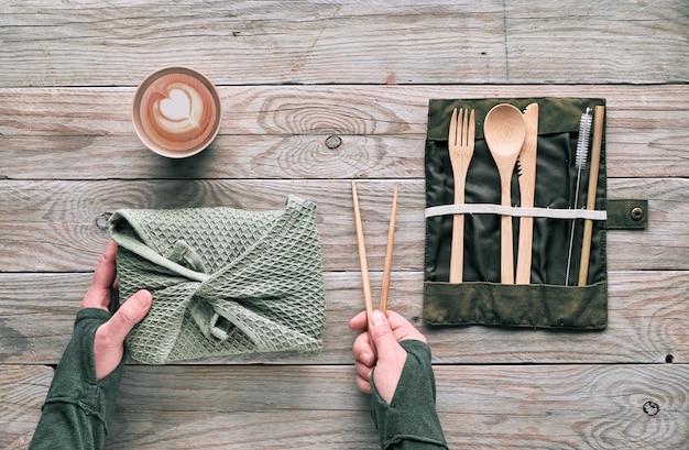 Плоская планировка, обед без отходов - набор многоразовых деревянных столовых приборов, коробка для завтрака из текстиля, кофе в многоразовой чашке. устойчивый образ жизни, руки держат ланч-бокс и бамбуковые палочки для еды.