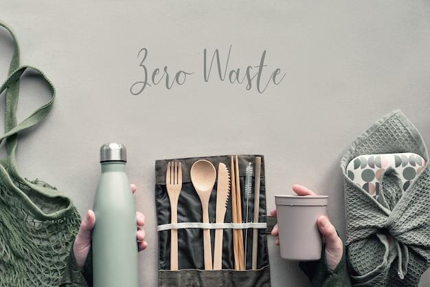創造的なトップビュー、ゼロ廃棄物ランチコンセプト。竹カトラリーがセットされた平置きのランチボックス、再利用可能なボックス、キャンバスバッグ、ペーパークラフトのコーヒーツーゴーカップの手。テキスト「ゼロ廃棄物」。