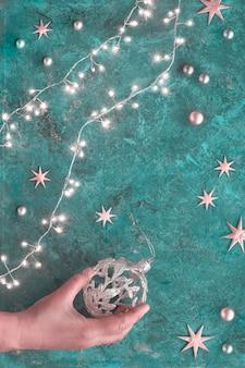 クリスマスや新年フラットターコイズブルーの暗い背景に背景を置きます。クリスマスガーランド、黄金のつまらないもの、星に平面図フラットレイアウト。華やかな小物を持っている手。メリークリスマス、そして、あけましておめでとう!