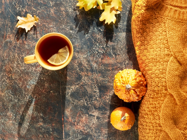 Осенняя квартира лежала с желтым свитером, декоративными тыквами, дубовыми листьями и чашкой чая с лимоном на темном