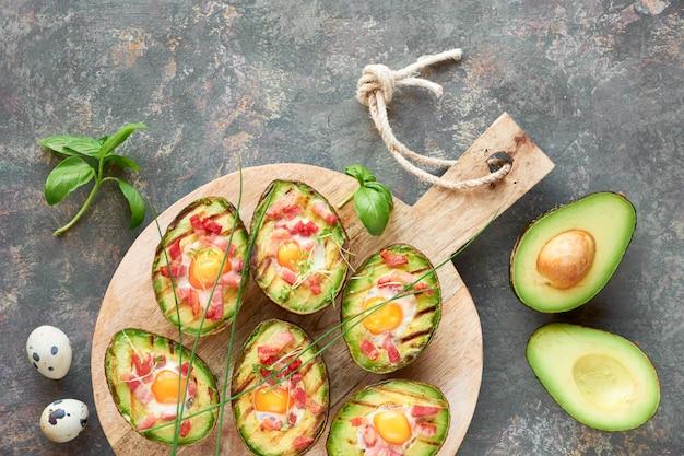 Вид сверху на жареные авокадо лодки с беконом и перепелиными яйцами, плоские лежал на темном деревенском дереве