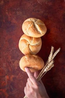 さびた丸いパンのピラミッドは、小麦の穂を持っている手でロールします。
